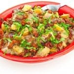 Red, White, and Blue Potato Salad in red bowl covered with chopped fresh basil