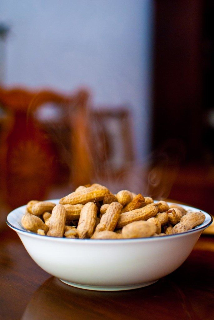 Steaming bowl of peanuts in a white bowl