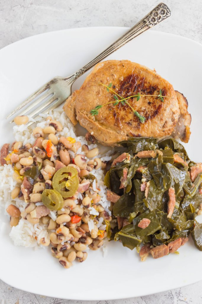 White plate with seared pork chop, instant pot collard greens, ad hoppin john.