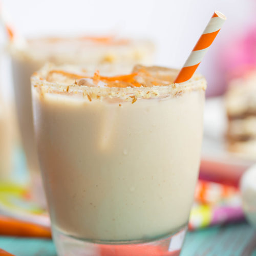 Close up of carrot cake white russian rimmed with cream cheese and garnished with carrot strips and an orange and white striped straw