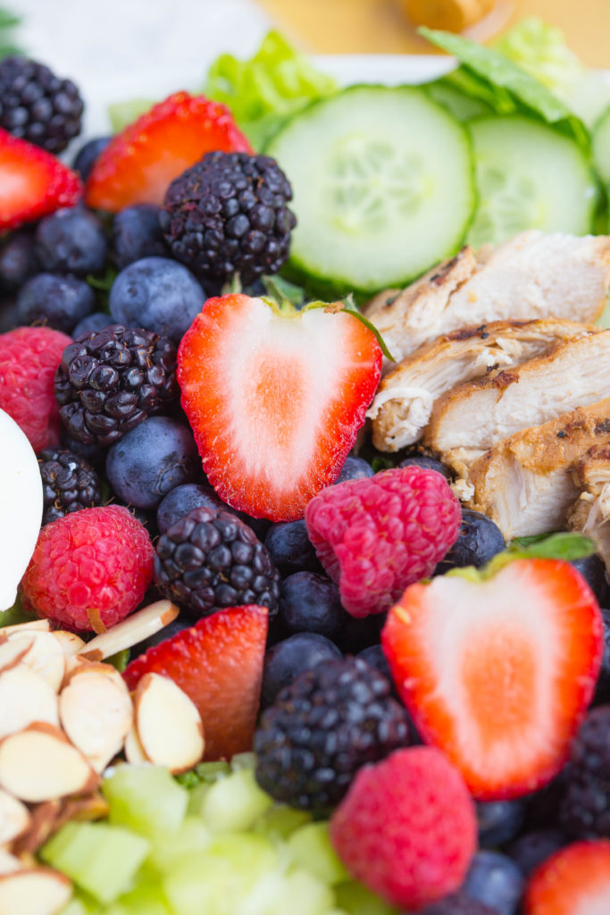 Close up of mixed berries on salad with sliced almonds, celery, and cucumber
