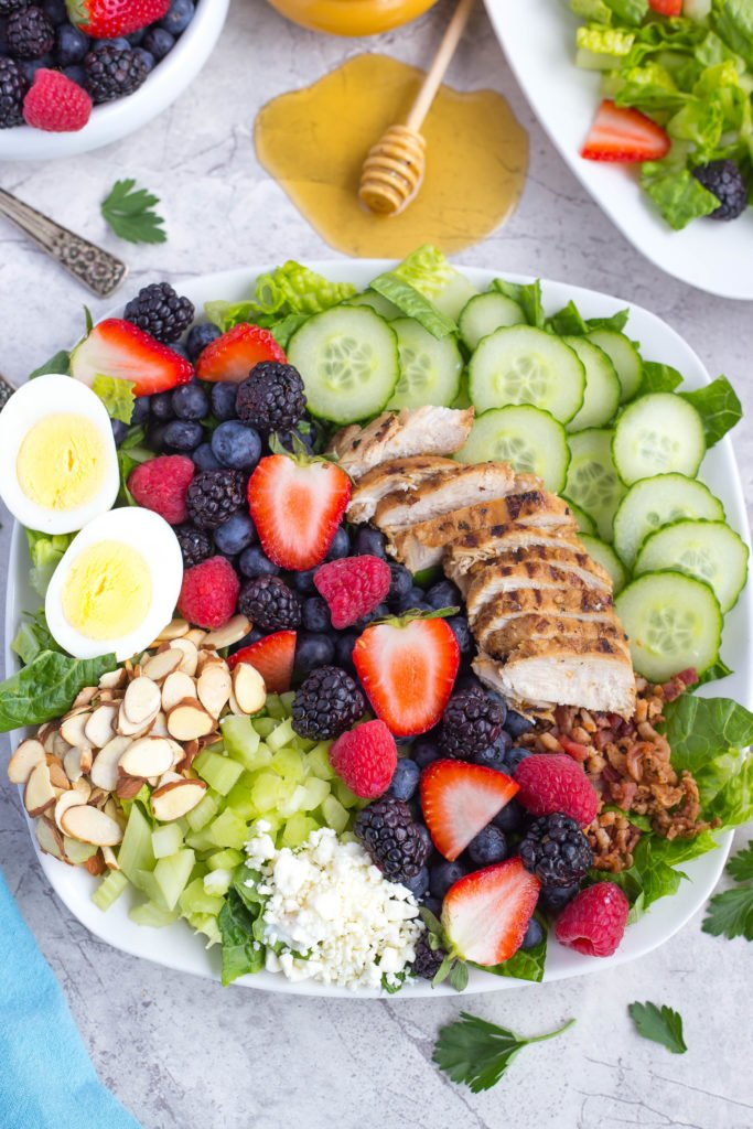 Green Cobb Salad With slivered almonds, a hard boiled egg, mixed berries, grilled chicken, sliced cucumber, and chopped bacon