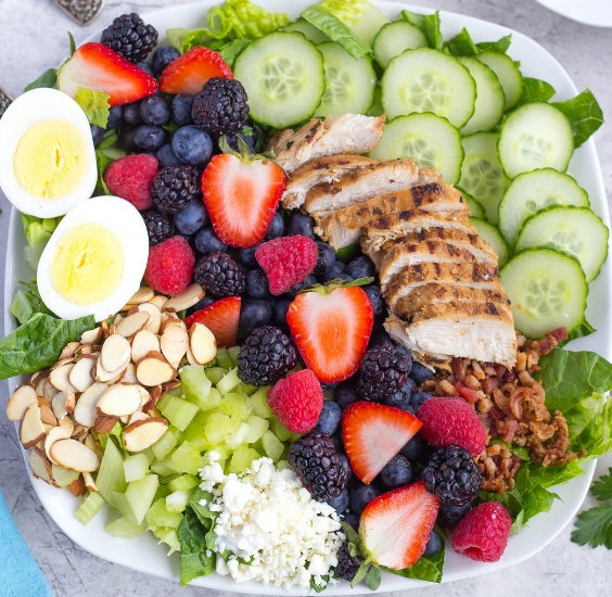 Close up of mixed berry cobb salad with berries, hard boiled egg, grilled chicken, sliced almonds, sliced cucumbers, celery, and bacon