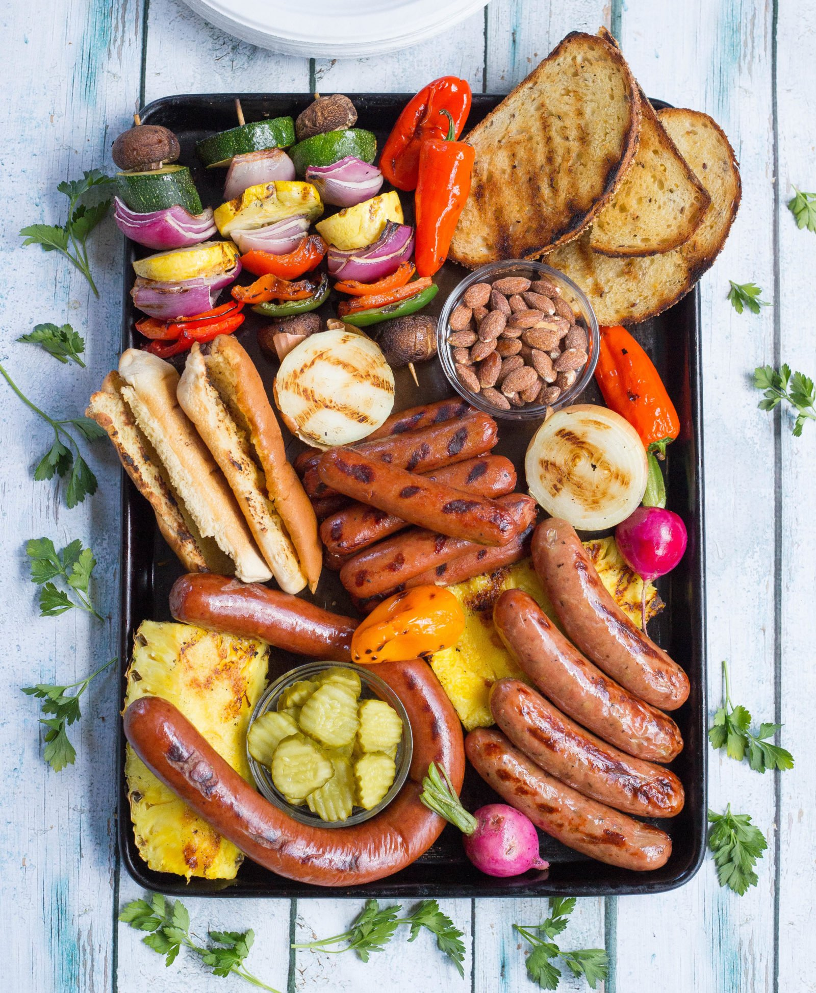 Platter with grilled hot dogs, sausages, pickles, pineapple, peppers, almonds, and bread