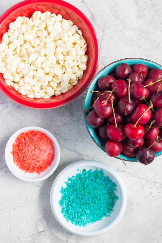 4th of July Desserts: White chocolate chips in red bowl, fresh cherries in blue bowl, blue Pop Rocks in small blue pinch bowl, red Pop rocks in even smaller pinch bowl