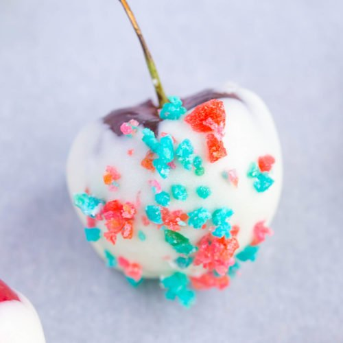 Close up of white chocolate covered cherry 4th of July Cherry Bombs with red and blue pop rocks