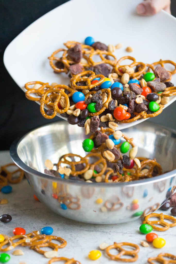Pretzels, peanuts, raisins, and peanut butter M&Ms on a white plate pouring into a silver bowl