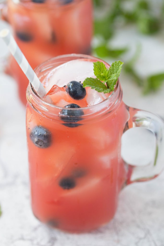 Close up of watermelon rum runner cocktail with blueberries and a sprig of fresh mint