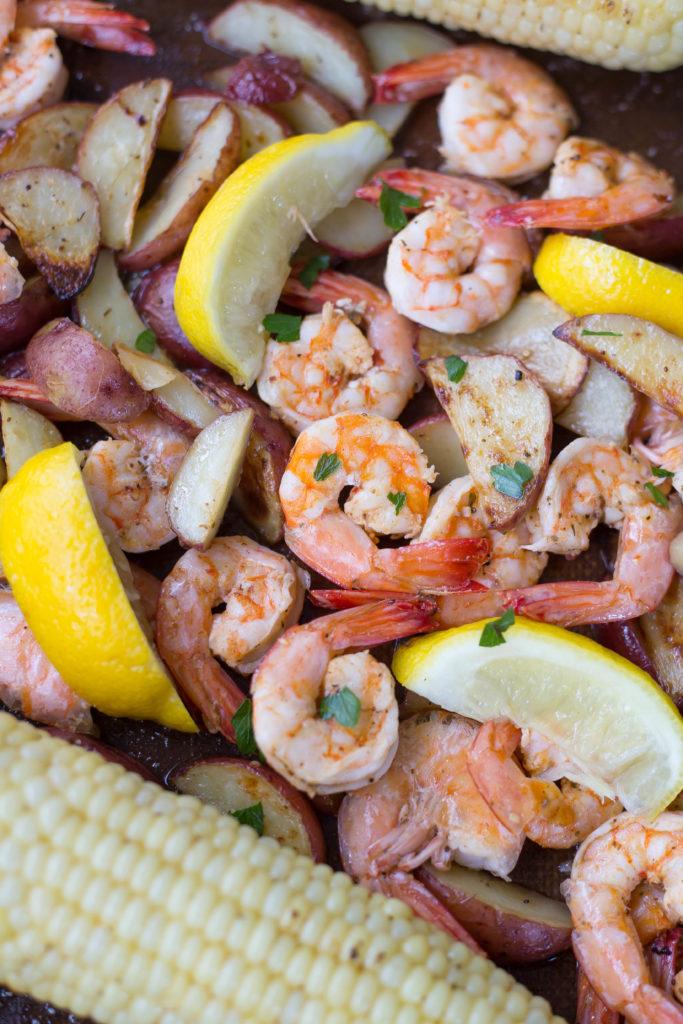 Cooked shrimp, lemon wedges, potatoes, and sausage on sheet pan