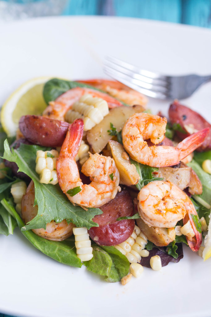 Close up of shrimp, potatoes, and sausage on green leaf lettuce