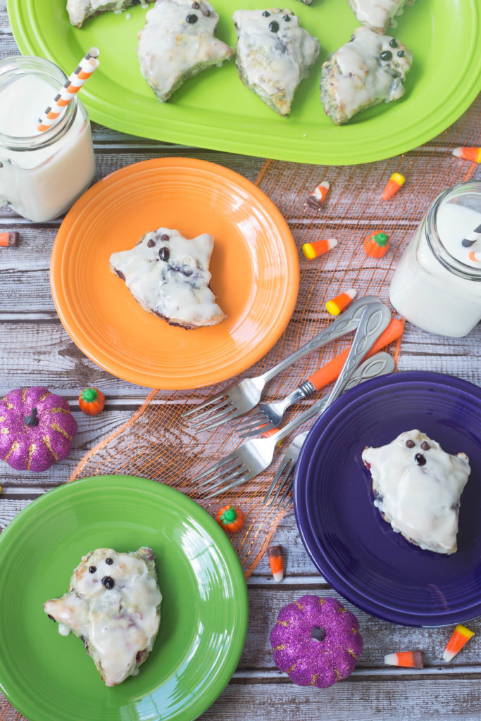 Overhead shot of biscuits decorated like ghosts on lime green, dark purple, and orange fiestaware.