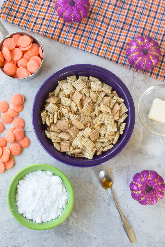 Overhead shot of chex cereal in purple bowl, powedered sugar in green bowl, and orange candy melts in silver measuring cup