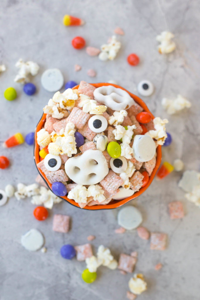 Overhead flat lay shot of popcorn mix with white pretzels and orange muddy buddies