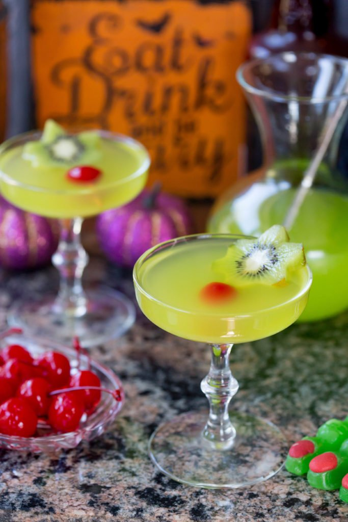 Glowing green witches brew cocktails garnished with a kiwi and a cherry