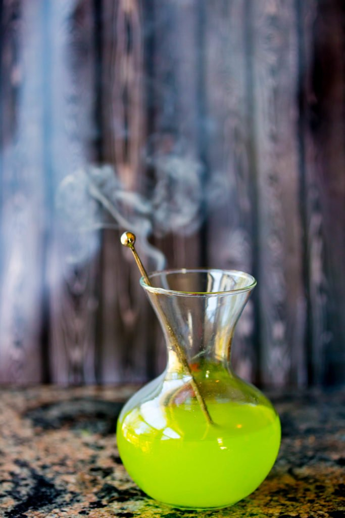 Glowing green witches brew in glass jar with silver stirrer and smoke