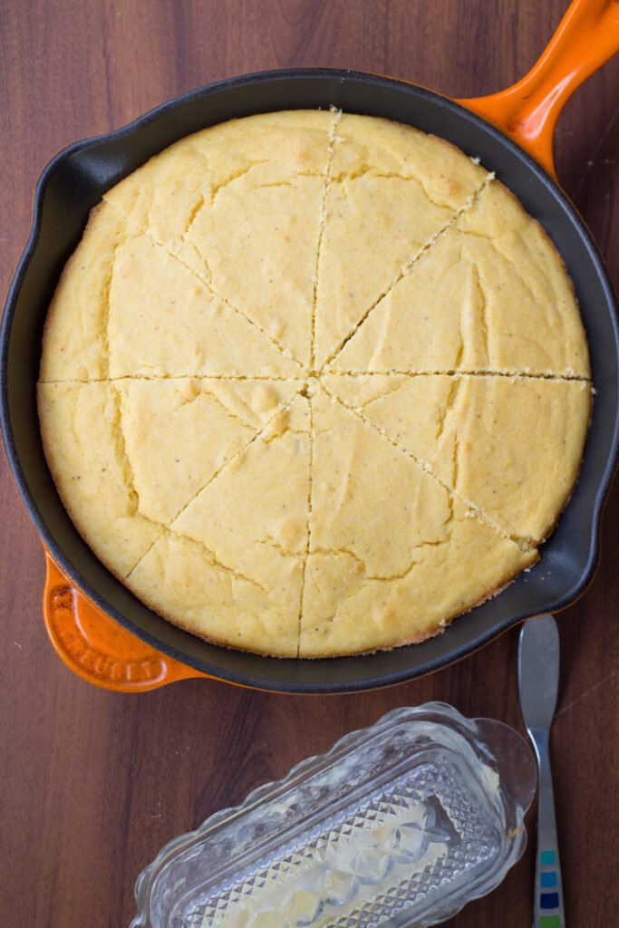 Full pan of buttermilk cornbread in orange cast iron skillet