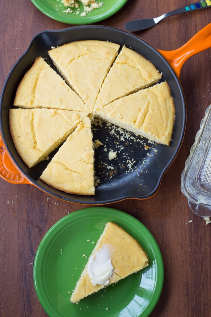 slices of buttermilk cornbread in orange cast iron pan with one slice of cornbread on green plate