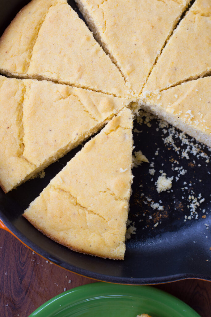 close up of triange slice of buttermilk cornbread in black cast iron skillet