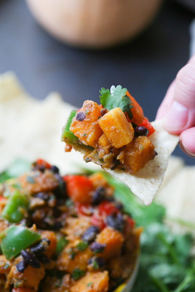 Hand picking up chip with scoop of roasted butternut squash salsa