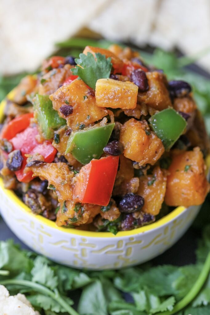 Chunks or roasted butternut squash, red and green bell peppers, and black beans, in a small bowl with yellow trim.