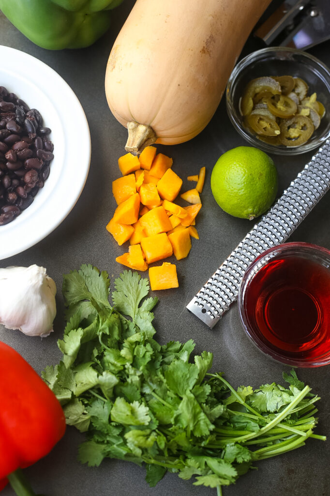 All of the ingredients for roasted butternut squash and black bean salsa ingredients: whole butternut squash, fresh limes, black beans, red wine vinegar, fresh bell peppers, fresh garlic.