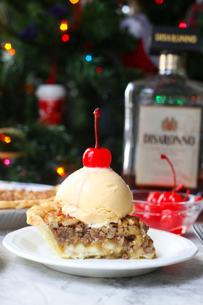 Slice of white chocolate amaretto pecan pie with giant scoop of vanilla ice cream and a red cherry with amaretto bottle in the background