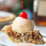 Close up image of white chocolate amaretto pecan pie with melted vanilla ice cream topped with a red cherry