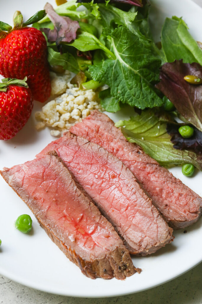 Close up pics of easy London Broil on white place with salad in the background