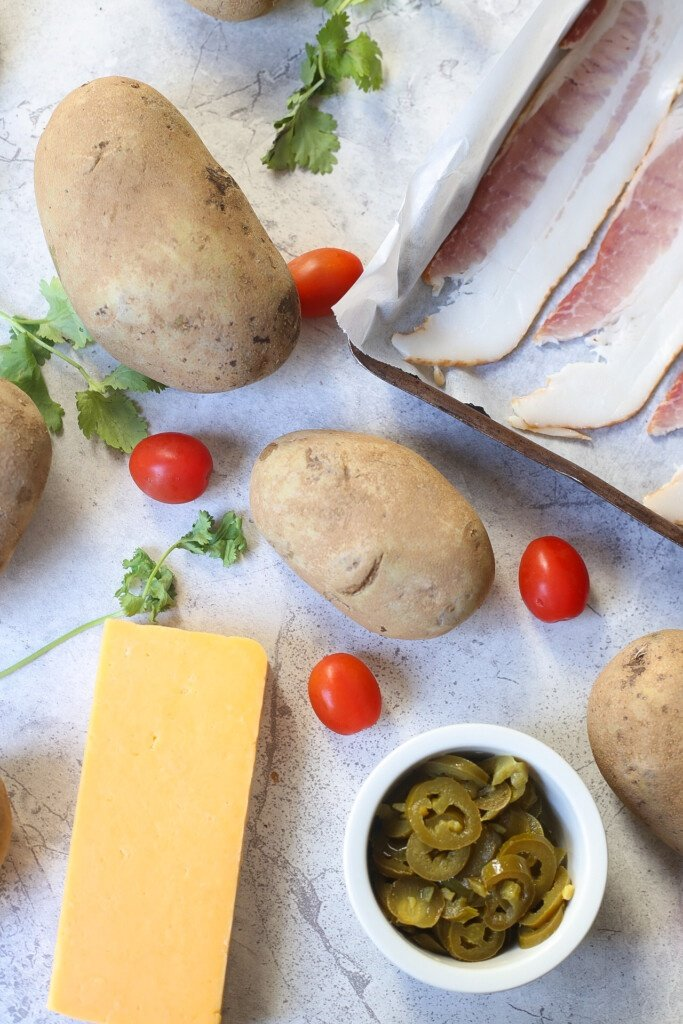 Flat lay photo of potatoes, jalapeno, cheddar cheese, tomatoes, and potatoes
